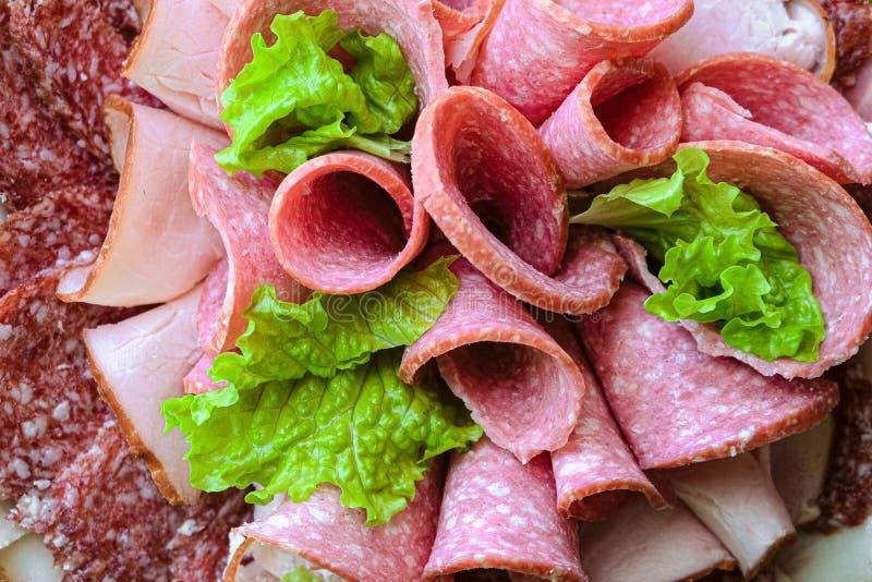 Jambon coup? en tranches et petits pains de saucisse fum?s crus avec des feuilles de laitue images stock
