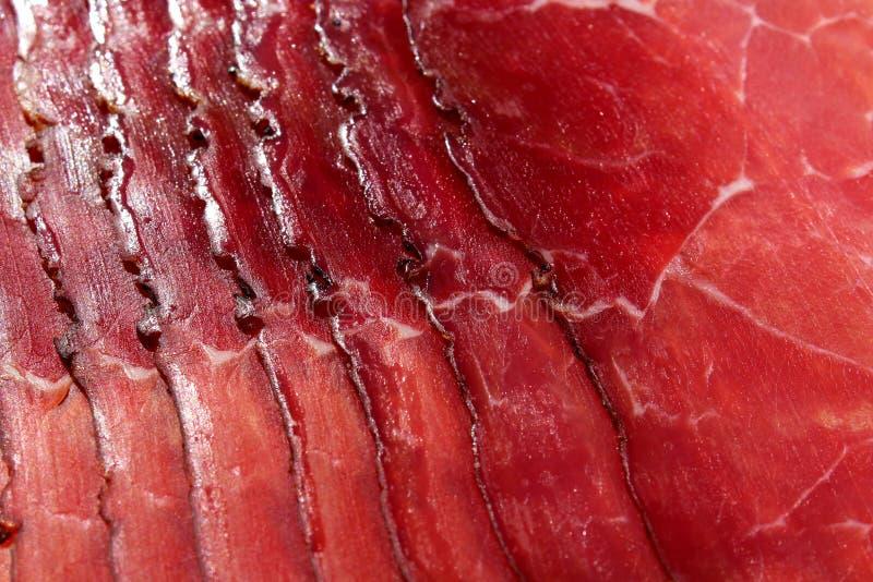 Jambon fumé Tranches italiennes de viande rouge de point sur le fond blanc Tranches de viande de beaf de Prosciutto comme texture photo libre de droits
