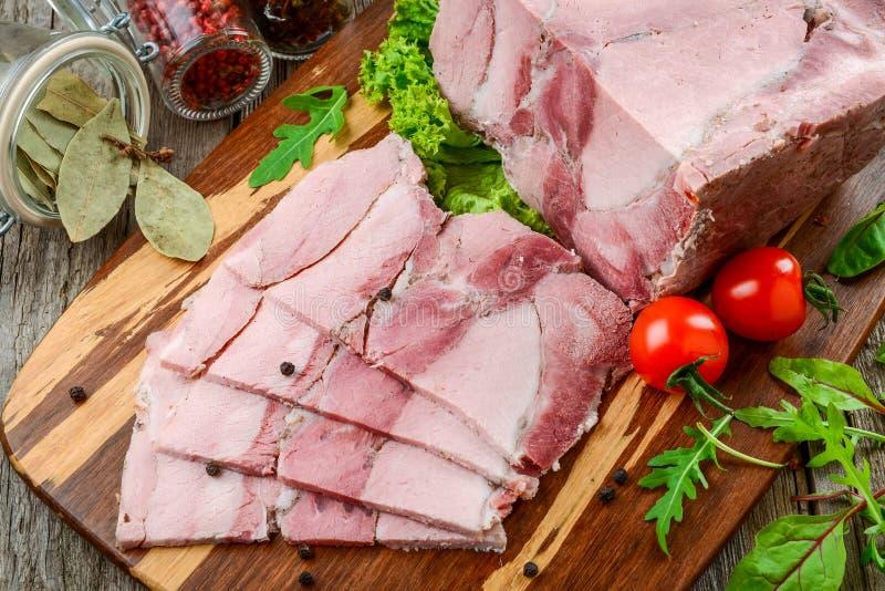 Jambon rôti de porc avec des légumes de couteau et de rôti de cuisine sur le fond rustique foncé image libre de droits