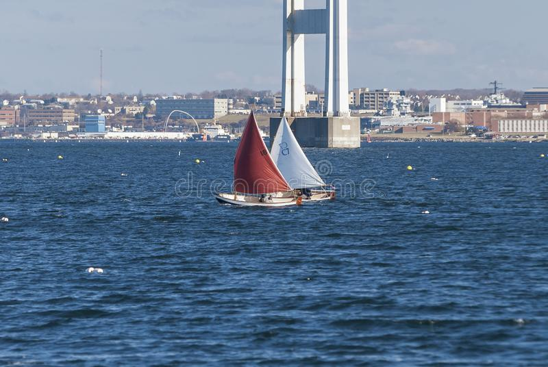 Sailboats racing on winter day. Jamestown, Rhode Island, USA - January 12, 2008: Pair of small sailboats in winter race off Jamestown with Newport Bridge in stock photography