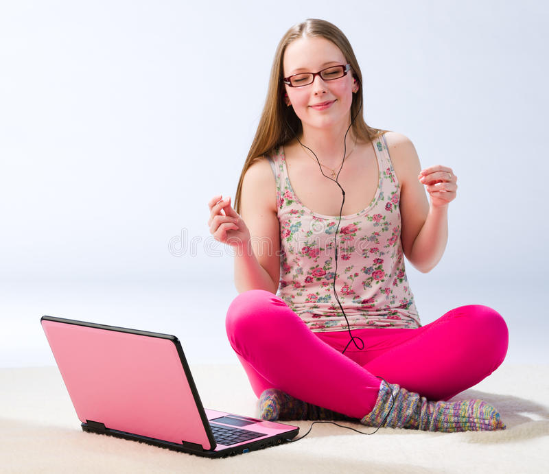 Jamming girl. A young girl jamming and sitting on the floor with a laptop stock photo