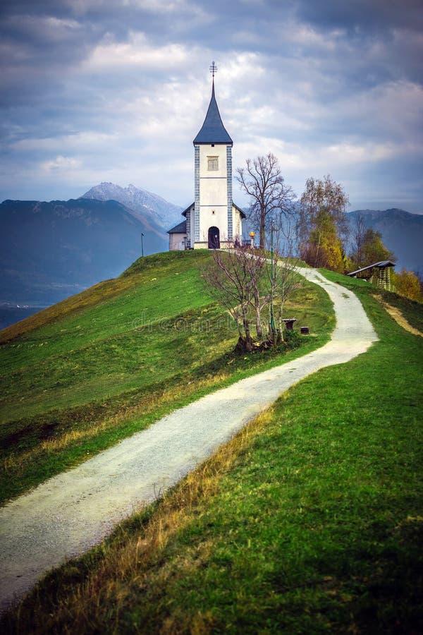 Jamnik, Σλοβενία - η όμορφη εκκλησία του ST Primoz στη Σλοβενία κοντά σε Jamnik με τις ιουλιανές Άλπεις στοκ εικόνα