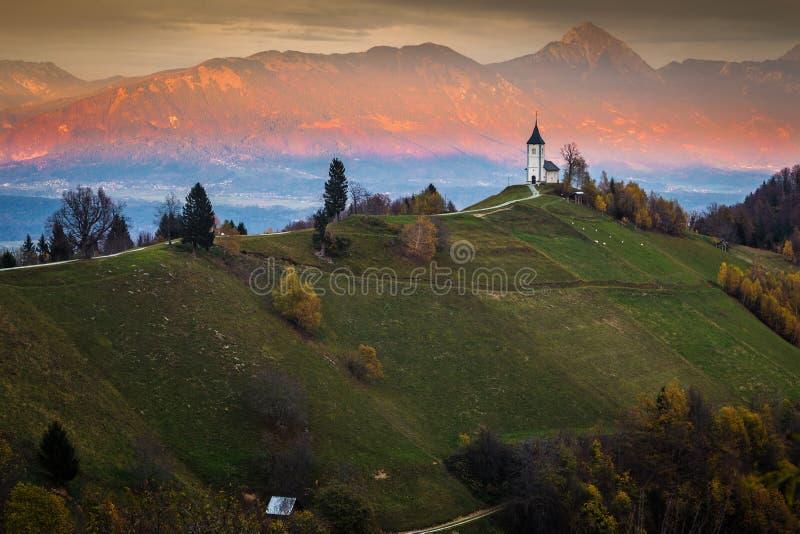 Jamnik, Eslovenia - puesta del sol de oro hermosa en la iglesia del St Primoz de Jamnik fotos de archivo libres de regalías