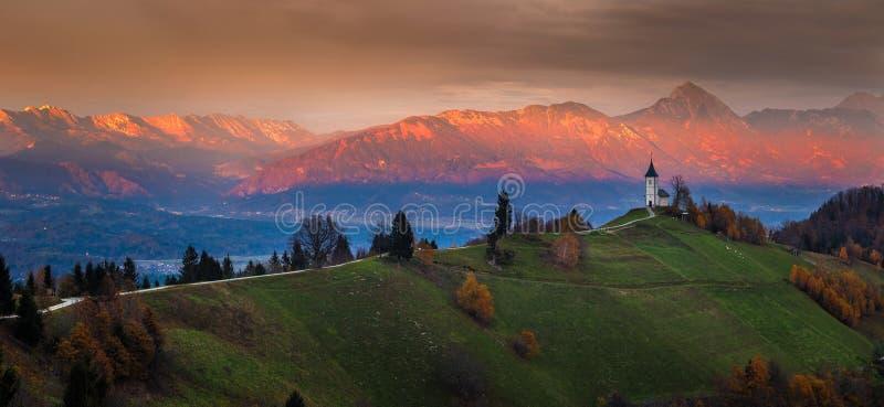 Jamnik, Slovenië - Mooie gouden zonsondergang bij de kerk van Jamnik St Primoz royalty-vrije stock fotografie