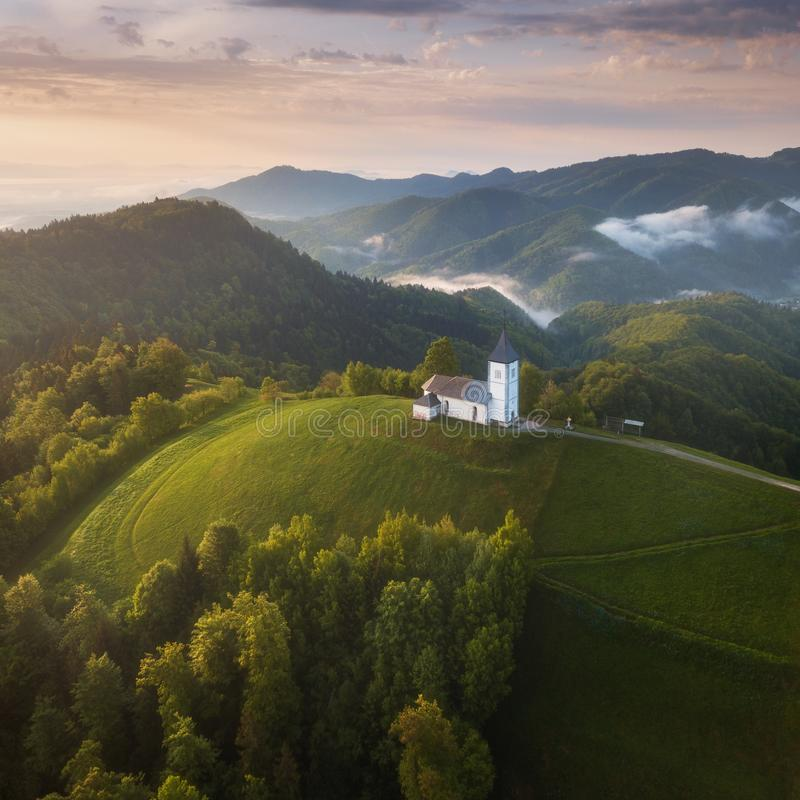 Jamnik, Slovenia - Aerial view the church of St. Primoz in Slovenia near Jamnik and Bled with beautiful clouds and Julian Alps. royalty free stock photos