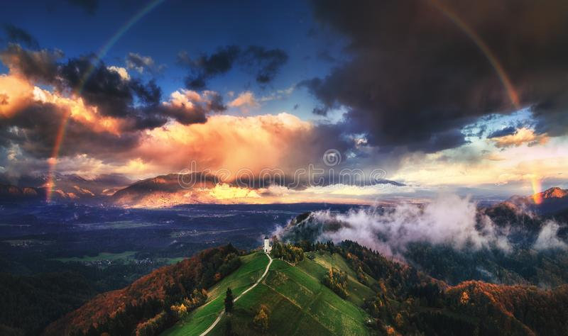 Jamnik, Slovenia - Aerial view of rainbow over the church of St. Primoz in Slovenia near Jamnik with beautiful clouds and Julian stock photos