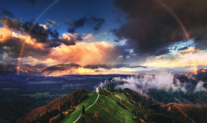 Jamnik Slovenien - flyg- sikt av regnbågen över kyrkan av St Primoz i Slovenien nära Jamnik med härliga moln och Julian arkivfoton
