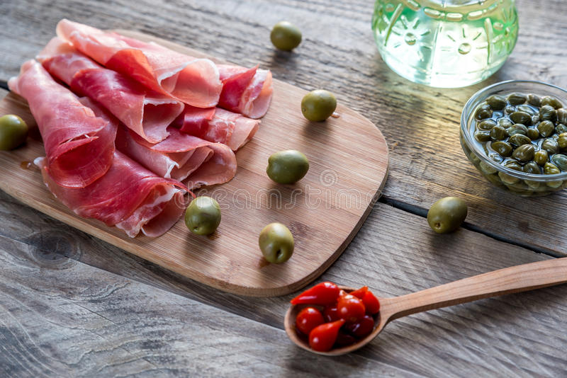 Jamon with capers and olives on the wooden board royalty free stock photos
