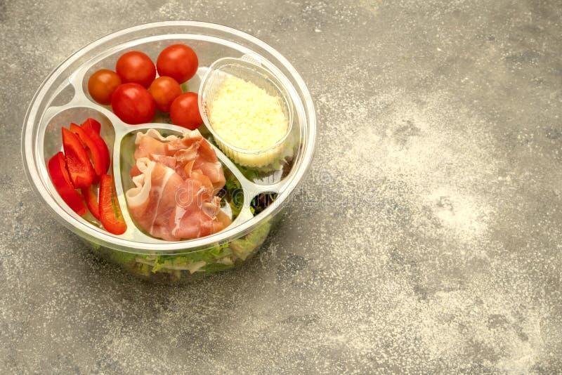 Υγιές γρήγορο φαγητό σε ένα διαφανές εμπορευματοκιβώτιο Φυτική σαλάτα για γρήγορα να μαγειρεψει με τις ντομάτες, τα πιπέρια κουδο στοκ φωτογραφία με δικαίωμα ελεύθερης χρήσης