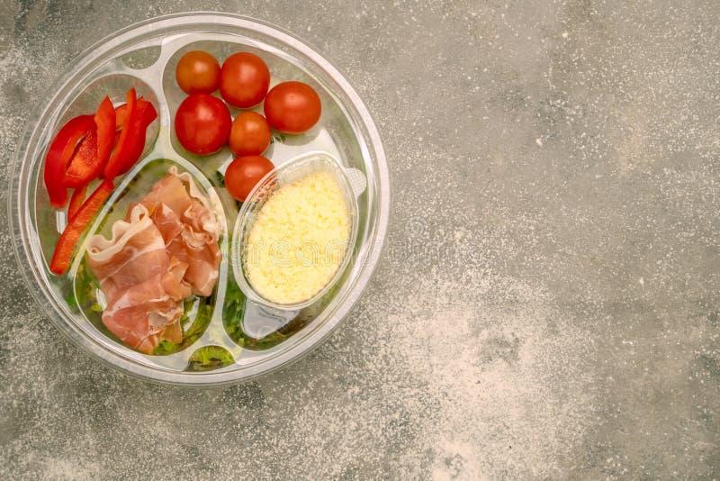 Υγιές γρήγορο φαγητό σε ένα διαφανές εμπορευματοκιβώτιο Φυτική σαλάτα για γρήγορα να μαγειρεψει με τις ντομάτες, τα πιπέρια κουδο στοκ φωτογραφίες