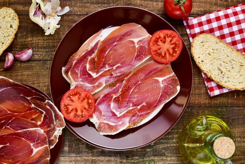 Jamon español del tomate y de la estafa de la cacerola, pan con el tomate y serrano ha imágenes de archivo libres de regalías