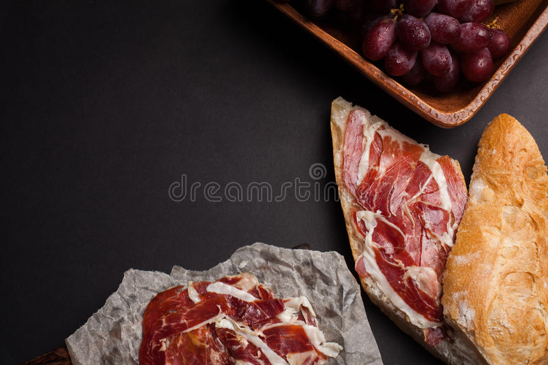 Jamon Iberico with white bread, olives on toothpicks and fruit on a dark background. Top view with copy space stock photography