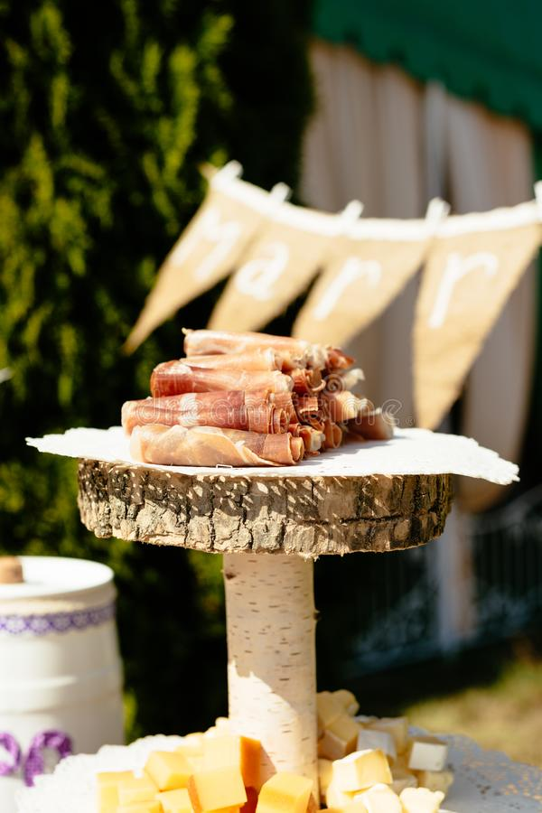 Jamon meat rol with chess on served wooden board royalty free stock photography
