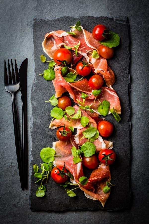 Jamon serrano,蕃茄,芝麻菜沙拉,黑石板岩板 库存图片