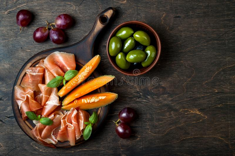 Jamon serrano or prosciutto with melon and olives over rustic wooden background. Italian or spanish antipasti stock photo
