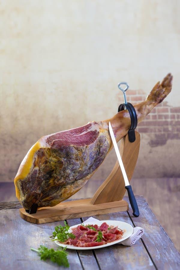 Jamon Serrano van Jamon Traditionele Spaanse ham met messen dichte omhooggaand Droog genezen Spaanse varkensvleesham in een plaat royalty-vrije stock foto