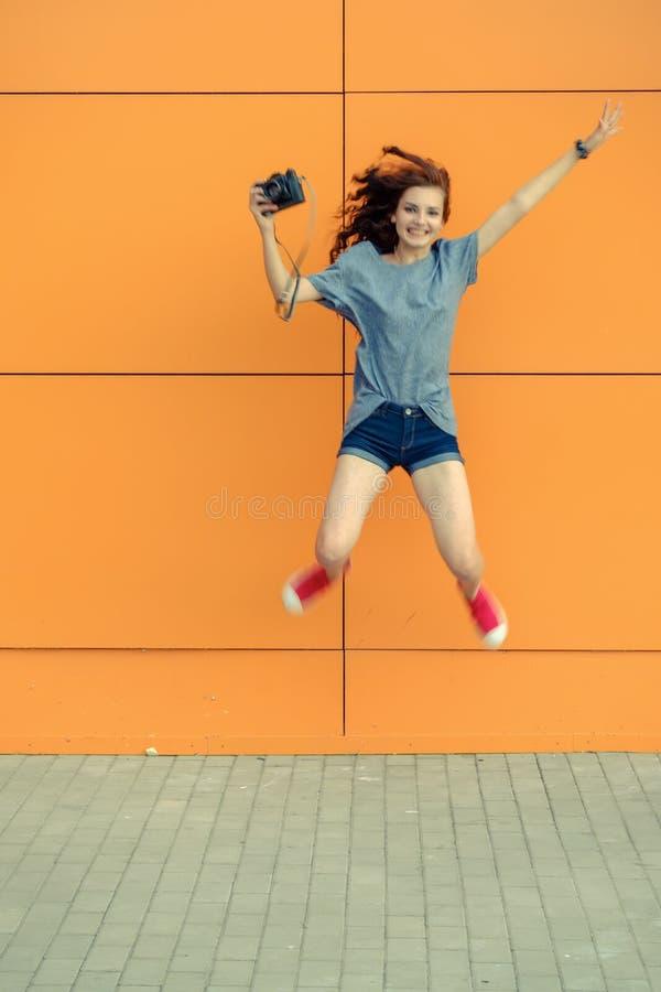 jamping与在橙色墙壁前面的葡萄酒照相机的俏丽的女孩 库存照片