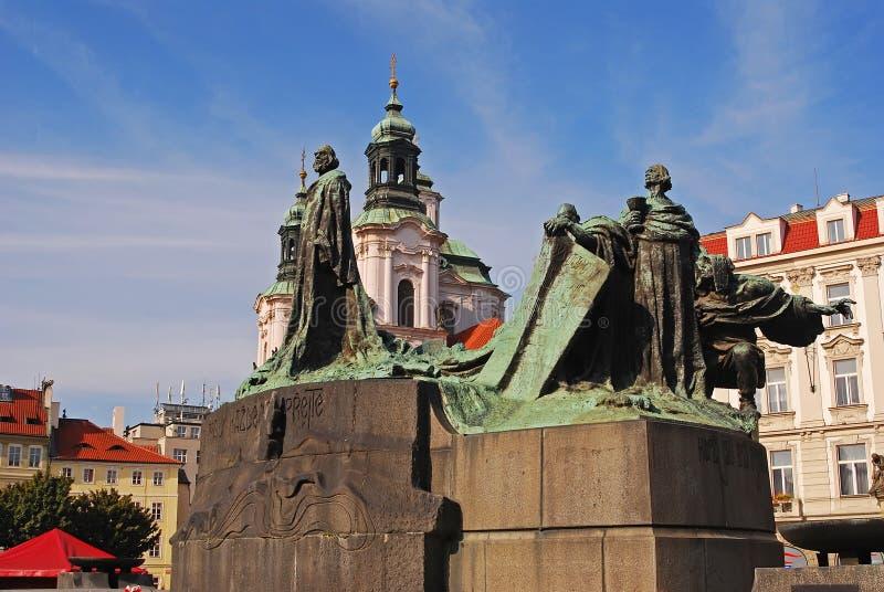 Jan Hus Memorial Statue mit Heiligem Nicholas Church im Hintergrund lizenzfreie stockfotos