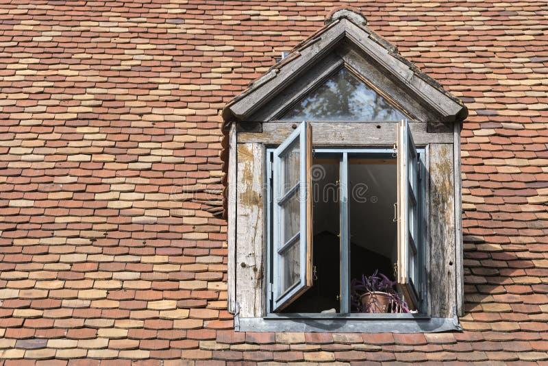 Janela aberta em um trapeira velho em um telhado com histórico foto de stock