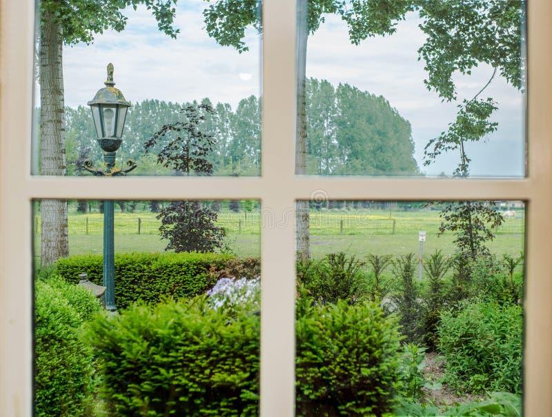 Janela acolhedor branca clássica com opinião verde do prado da paisagem imagens de stock