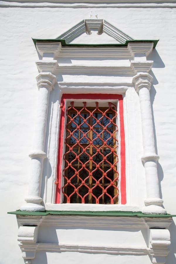 Janela antiga com as barras vermelhas decoradas com o telhado de guarda-chuva das colunas foto de stock royalty free