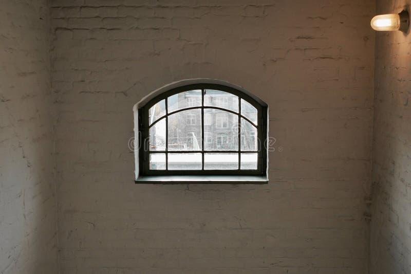 Janela arqueada em uma sala branca desencapada do tijolo imagem de stock royalty free