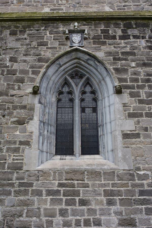 Janela arqueada pequena na parede de pedra da igreja fotografia de stock