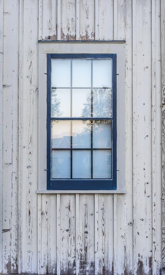 A janela azul em um branco velho lavou o celeiro imagem de stock