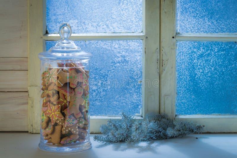 Janela azul fria com as cookies no frasco para o Natal imagens de stock royalty free