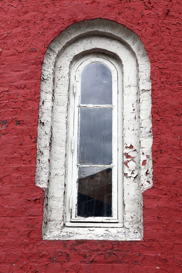 Janela branca decorativa em uma parede vermelha velha imagens de stock