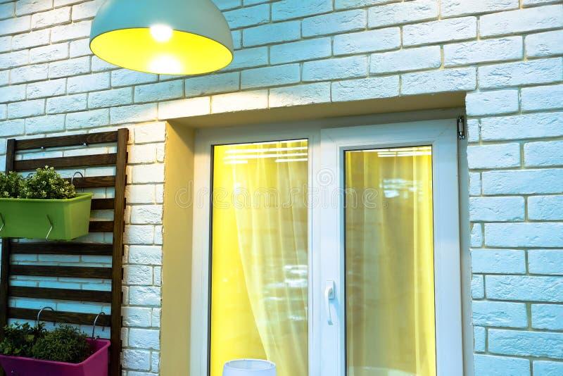 Janela branca no fundo branco da parede de tijolo Uma lâmpada brilha acima da janela Tenha flores de Windows Atmosfera acolhedor, imagens de stock