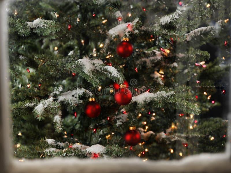 Janela coberto de neve com árvore de Natal e luzes de incandescência fotos de stock royalty free