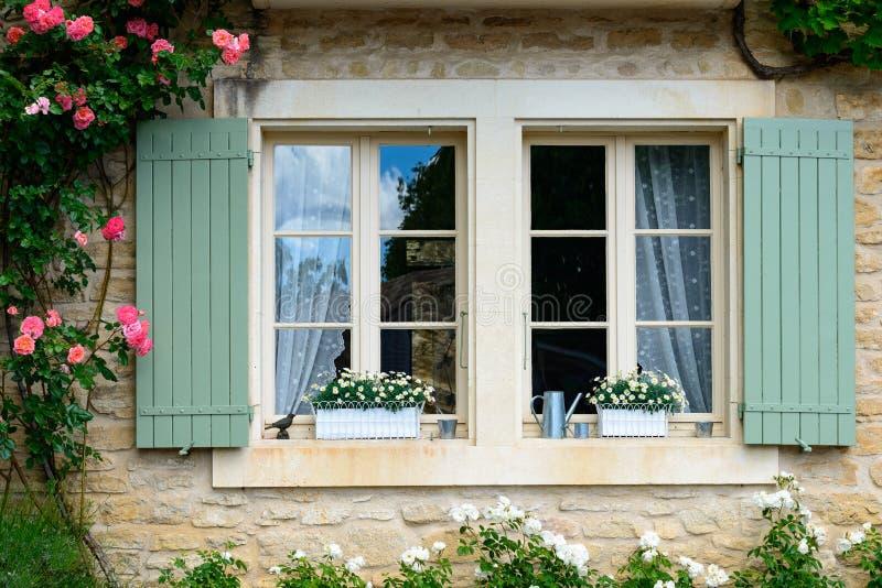 janela com as cortinas e o obturador cercados por rosas fotografia de stock royalty free
