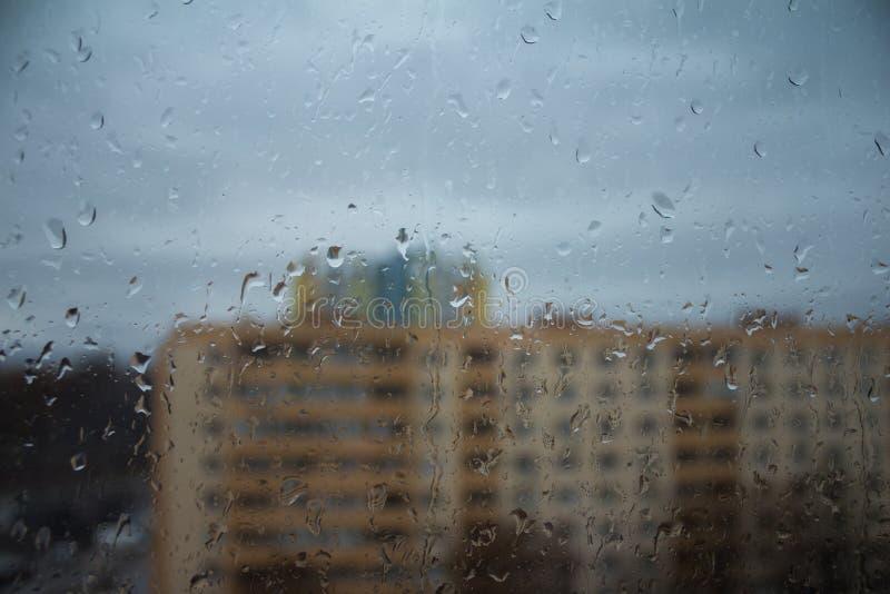 Janela com gotas e construções da chuva foto de stock