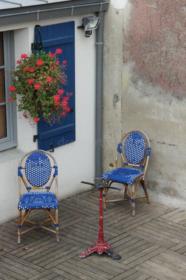 Janela com os obturadores azuis no couryard com cadeiras foto de stock