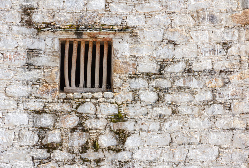 Janela da cela com barras de madeira em uma parede de tijolo branca fotografia de stock royalty free