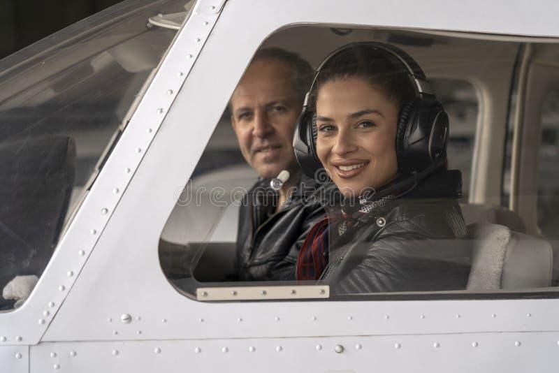 Janela de cabina do piloto fêmea de sorriso de Looking Through The do piloto e do instrutor do voo imagem de stock royalty free