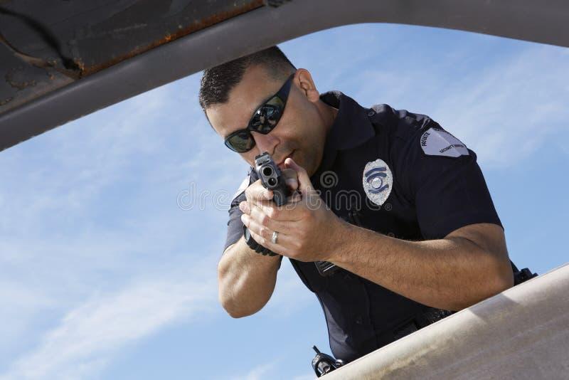 Janela de carro de Aiming Gun Through do agente da polícia fotografia de stock