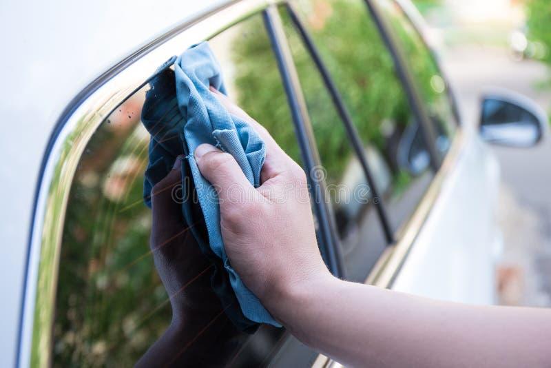 Janela de carro de lavagem da mão masculina com pano do microfiber fotografia de stock