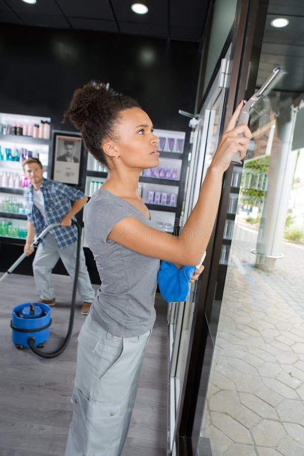 Janela de limpeza da mulher com o rodo de borracha no cabeleireiro imagens de stock