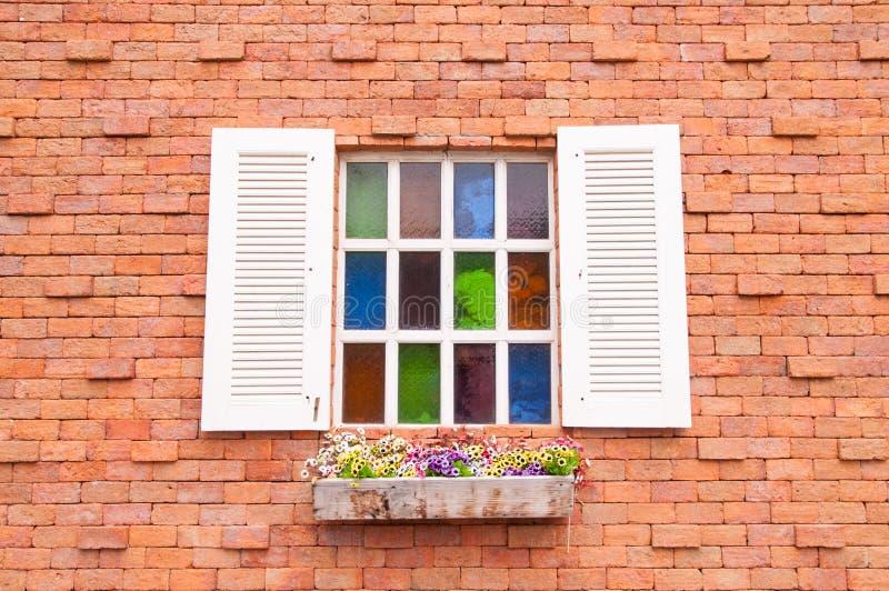 Janela de madeira bonita com a multi vidro da cor e parede de tijolo foto de stock royalty free