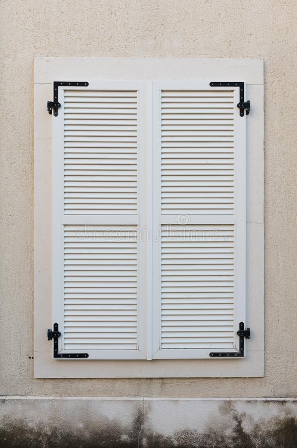 Janela de madeira fechada com os obturadores de madeira brancos Detalhes exteriores da casa foto de stock
