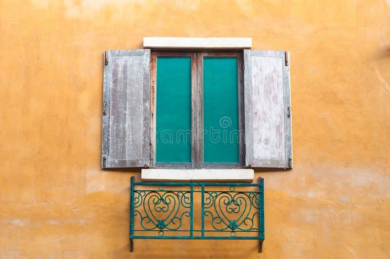 A janela de madeira satura sobre a casa amarela da parede imagem de stock royalty free