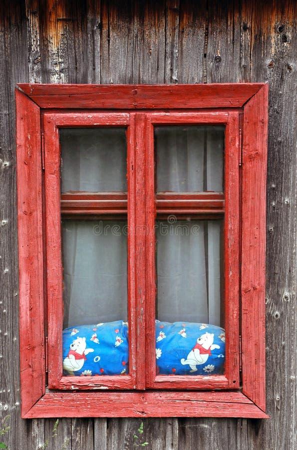 Janela de madeira vermelha em uma casa rústica fotos de stock