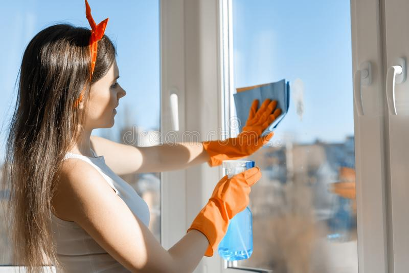 Janela de sorriso nova da limpeza da mulher, com o líquido de limpeza de janela do pulverizador e o pano nas luvas de borracha, l fotografia de stock royalty free