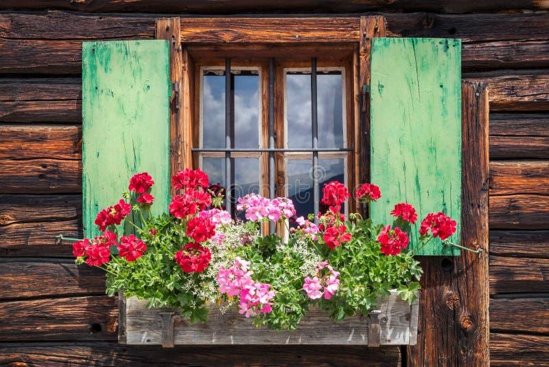 Janela de uma cabine de madeira velha nos cumes imagem de stock royalty free