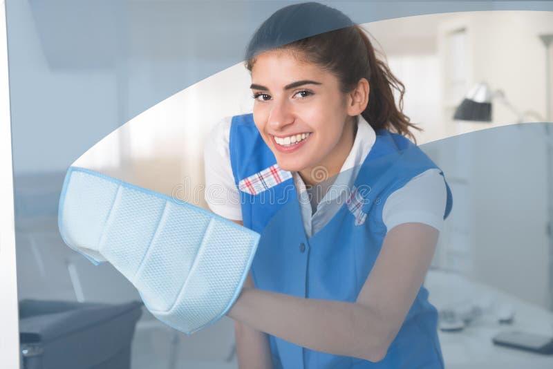 Janela de vidro de limpeza feliz de trabalhador fêmea com pano imagem de stock