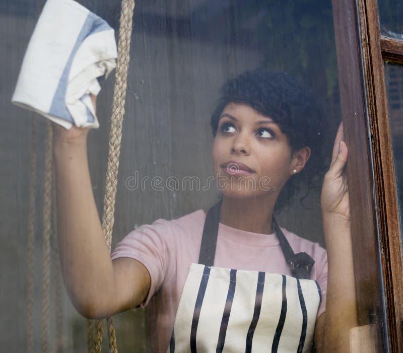 Janela de vidro de limpeza da ascendência africana fotos de stock