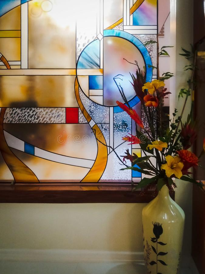 Janela de vitral colorida com arranjo de flor no vaso decorativo branco foto de stock royalty free