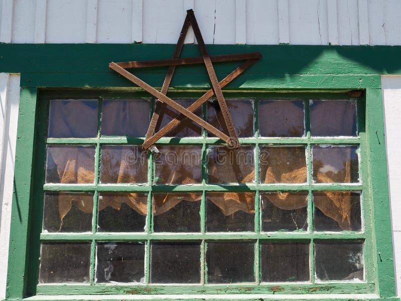 Janela dilapidada velha com a decoração de madeira da estrela imagem de stock